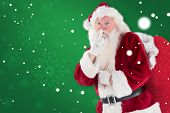 Santa asking for quiet with bag against green snowflake background