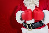 Mid section of santa with boxing gloves against red snowflake background