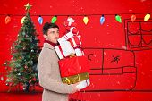 Young man with many christmas presents against red background