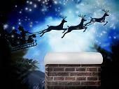 Composite image of santa flying his sleigh against christmas village under full moon