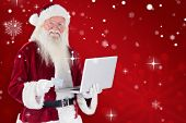 Santa pays with credit card on a laptop against red snowflake background