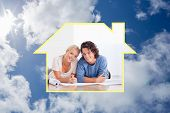 Cute couple moving in a new house against bright blue sky with clouds