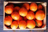 Fresh ripe mandarins in wooden box, on sackcloth background