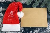 Santa red hat with branch of fir-tree, sheet of paper and snowflakes on color wooden background