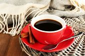 Cup of coffee on wicker stand near plaid on wooden table background