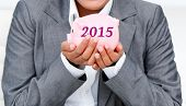 Close up of a smiling businesswoman holding a piggybank against 2015 in grey