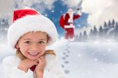 Cute little girl wearing santa hat against blue sky with white clouds