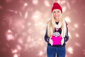 Festive blonde holding a gift against snowflake design shimmering on red