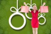 Pretty blonde in red dress holding shopping bags against blurred christmas background