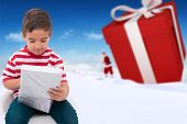 Cute little boy opening gift against bright blue sky over clouds