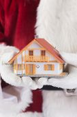 Santa holds a tiny house in his hands against red background