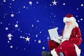 Santa sits and uses a laptop against blue snowflake background