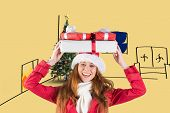 Festive redhead holding pile of gifts against yellow vignette