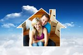 House frame in couple sitting on floor against bright blue sky with clouds