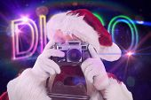 Santa is taking a picture against digitally generated colourful disco text
