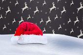 Santa hat on snow against grey reindeer pattern