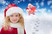 Cute girl in santa hat against bright blue sky over clouds