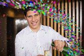 stock photo of champagne color  - Handsome man smiling at camera pouring champagne against colour curve - JPG