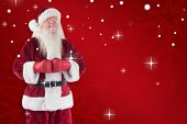 Santa Claus wears boxing gloves against red snowflake background