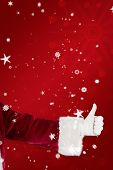 Father Christmas gives a thumb up against red snowflake background