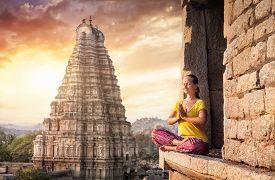picture of mudra  - Woman with Namaste mudra sitting near Virupaksha temple in Hampi Karnataka India - JPG