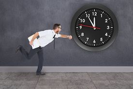 foto of running-late  - Geeky young businessman running late against grey room - JPG