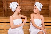 pic of sauna woman  - Two attractive women wrapped in towel talking to each other while relaxing in sauna - JPG