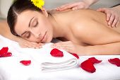 stock photo of therapist massage  - Attractive young woman with flower in head lying on front while massage therapist massaging her back - JPG
