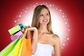 stock photo of starlet  - smile shopping woman with colorful bags on red background - JPG