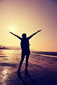 picture of open arms  - cheering young woman hiker open arms on sunrise beach - JPG