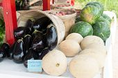 picture of honeydew melon  - Fresh melons for sale at a farm stand along with some fresh eggplants - JPG