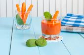 stock photo of light weight  - Healthy homemade carrot juice in glass and fresh carrots on light wooden background - JPG