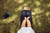 picture of big-foot  - High angle view of little baby sitting on her mother legs on grass in city park - JPG