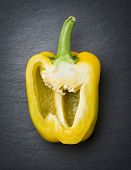 picture of yellow-pepper  - One sliced yellow sweet pepper half isolated on dark grey flagstone - JPG