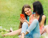 picture of laugh  - two happy women friends laughing and sharing social media pictures in a smart phone on picnic at the park lifestyle concept - JPG