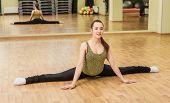 image of do splits  - Young slim woman doing side split in fitness class - JPG