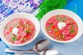 foto of beet  - beet soup with fresh dill on a blue wooden table - JPG