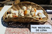 image of stall  - Firewood cooked bread in a basket on a market stall at the Medieval market Barbate Cadiz Province Andalusia Spain Western Europe - JPG