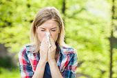 stock photo of blowing  - Woman with allergy symptom blowing her nose - JPG