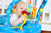 picture of playtime  - funny baby is playing in baby jumper - JPG
