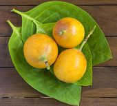 picture of passion fruit  - Passion fruits and Green Leaf on Wooden Background - JPG