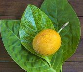 pic of passion fruit  - Passion fruits and Green Leaf on Wooden Background - JPG
