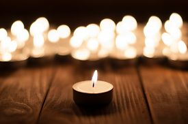 stock photo of compassion  - Group of burning candles on  black background - JPG