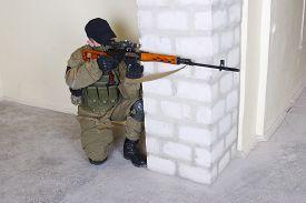 stock photo of sniper  - mercenary sniper with sniper rifle inside the building - JPG