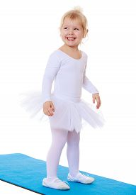 picture of leotard  - Cute little blonde girl in white gymnastic leotard stands on the Mat and smiles - JPG