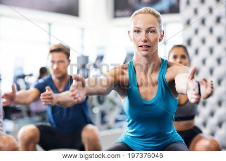 poster of Young woman exercising in gym with people in background. Fit woman exercising with stretched hands a