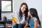Happy mother reading story book to little girl. Happy latin mother and daughter reading a book while poster