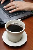 foto of coffee-cup  - Coffee cup on table with hands and laptop in the background - JPG