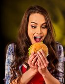 Woman eating french hamburger. Portrait of student consume fast food on table. Girl trying to eat ju poster