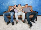stock photo of threesome  - Three tired young men sleep on a sofa - JPG